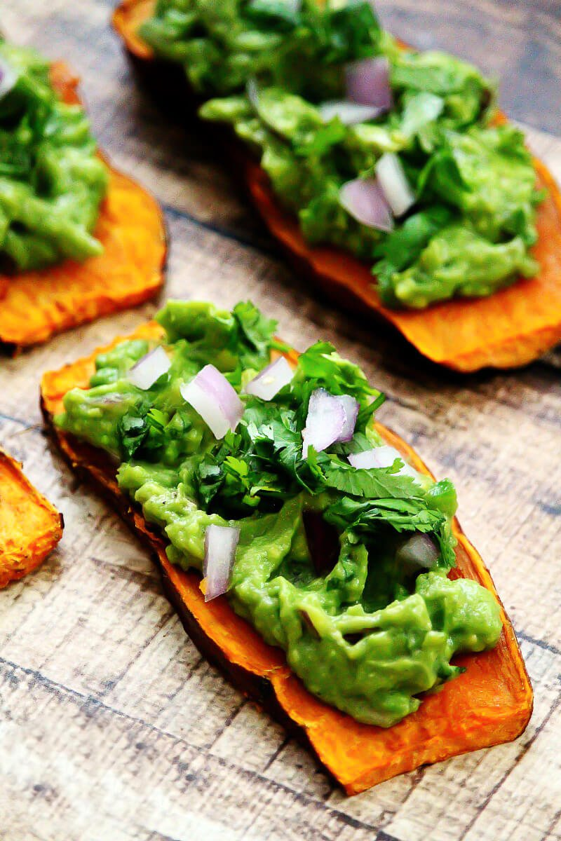 "Close-up image of a slice of sweet potato ""toast"" topped with spicy guacamole on a weathered wooden surface"