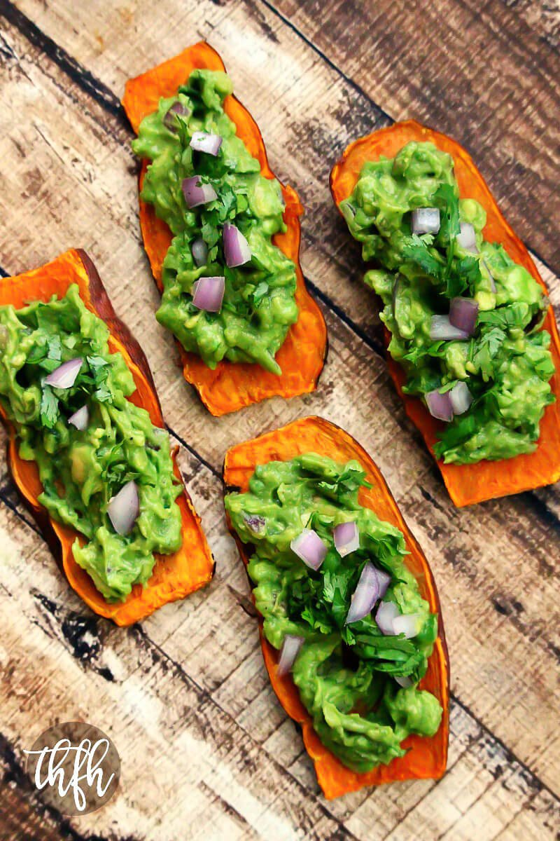 "Overhead image of four slices of sweet potato ""toast"" topped with spicy guacamole on a weathered wooden surface"