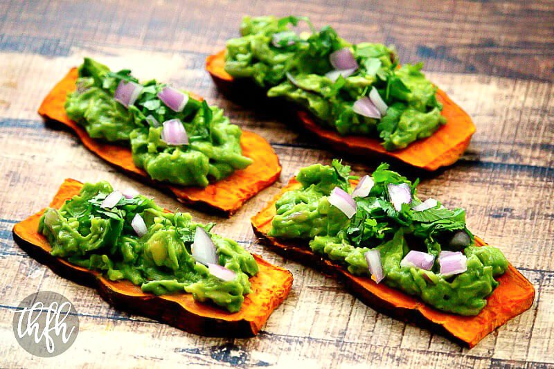 Horizontal image of four slices of sweet potato toast topped with spicy guacamole of a weathered wooden surface