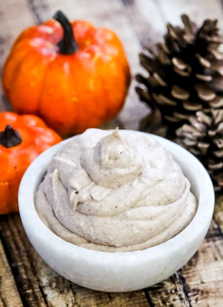 Vertical image of a small white marble bowl filled with The BEST Vegan Pumpkin Spice Mousse on a weathered wooden background