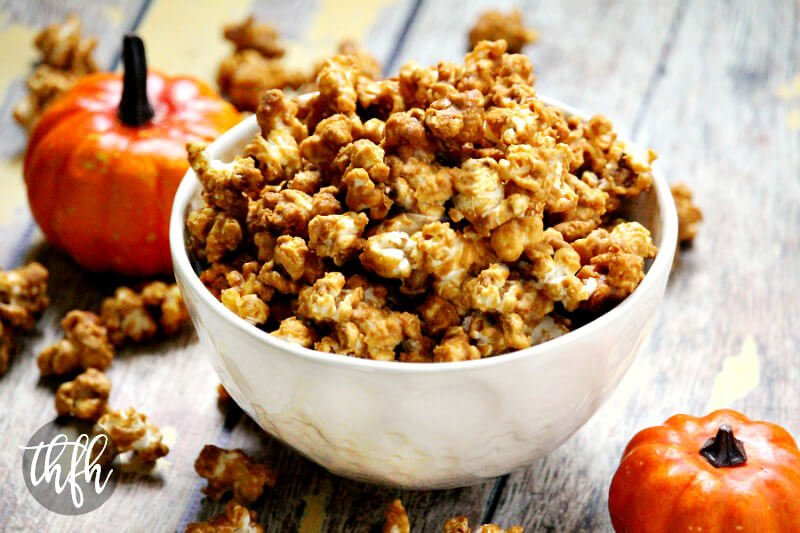 White bowl filled with The BEST Gluten-Free Vegan Pumpkin Spice Caramel Popcorn on a wooden surface with mini pumpkins in the background