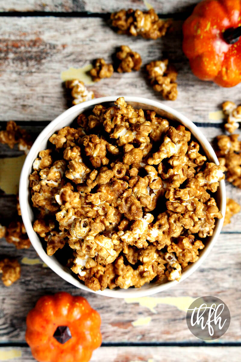 Overhead view of a bowl of The BEST Gluten-Free Vegan Pumpkin Spice Caramel Popcorn on a wooden surface with mini pumpkins in the background