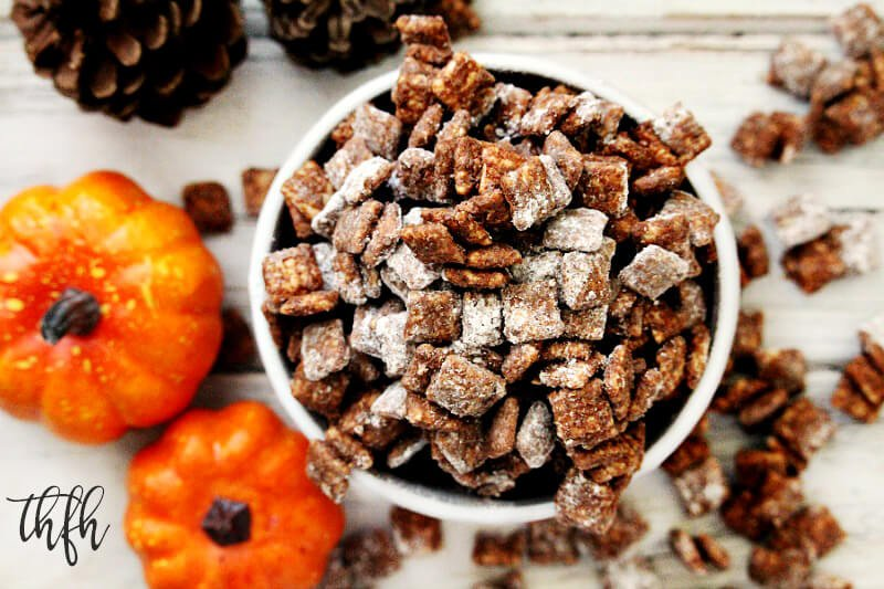 "Overhead image of a white bowl overflowing with Gluten-Free Vegan Pumpkin Spice ""Puppy Chow"" Muddy Buddies with pumpkins in the background"