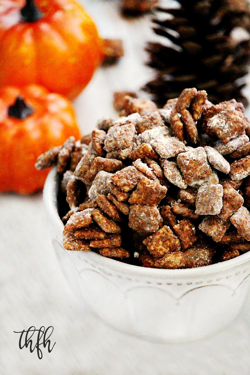 "Vertical image of a decorative white bowl filled with Gluten-Free Vegan Pumpkin Spice ""Puppy Chow"" Muddy Buddies and Fall decorations in the background"