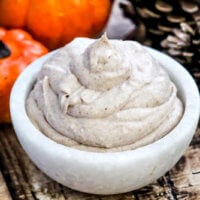 Horizontal image of The BEST Vegan Pumpkin Spice Mousse in a small white marble bowl on a weathered wooden surface