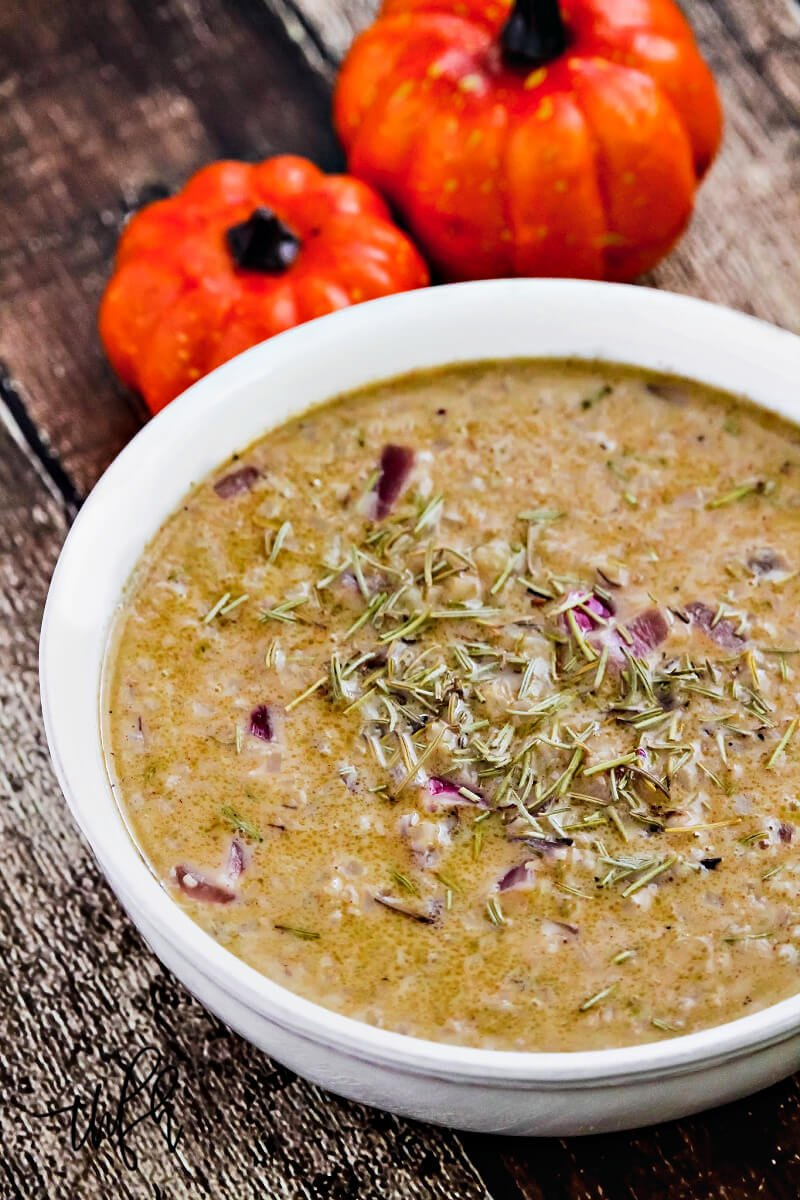 A vertical image of a white bowl filled with a creamy Gluten-Free Vegan Pumpkin Spice Cauliflower Rice Soup on a weathered wooden surface with two small pumpkins in the background