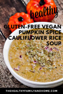 A white bowl filled with Gluten-Free Vegan Pumpkin Spice Cauliflower Rice Soup on a weathered surface with two small pumpkins in the background with text overlay