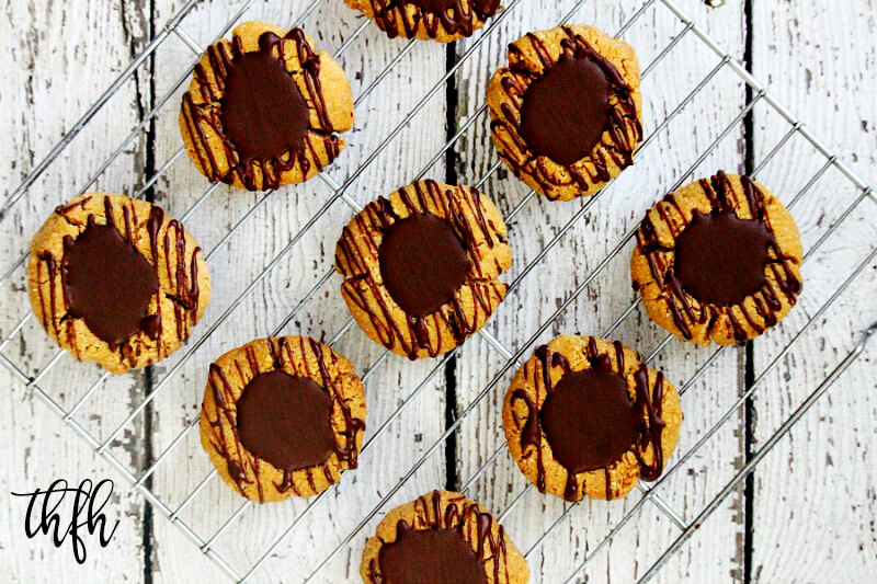 Overhead view of Gluten-Free Vegan Flourless Chocolate Peanut Butter Thumbprint Cookies on a wire cookie rack on top of a white wooden surface.