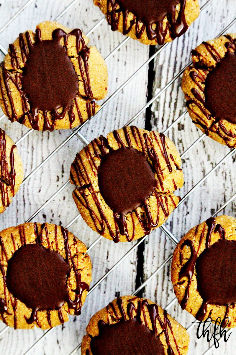 Overhead view of Gluten-Free Vegan Flourless Chocolate Peanut Butter Thumbprint Cookies on a wire cookie rack on top of a white wooden surface