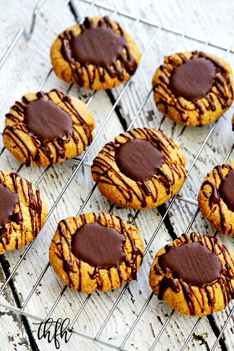 Angled overhead shot of Gluten-Free Vegan Flourless Chocolate Peanut Butter Thumbprint Cookies on a wire cookie rack on top of a white wooden surface