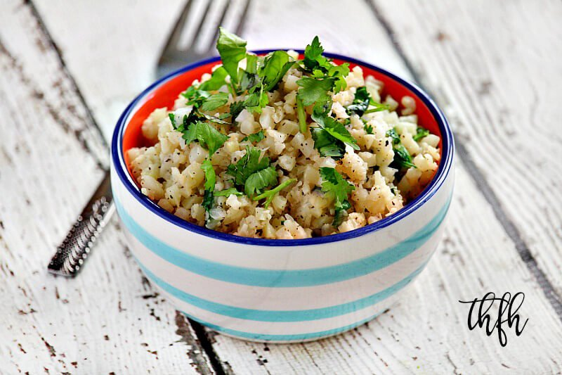 Horizontal image of Lectin-Free Vegan Cilantro and Lime Cauliflower Rice in a blue and white striped bowl on a white wooden surface