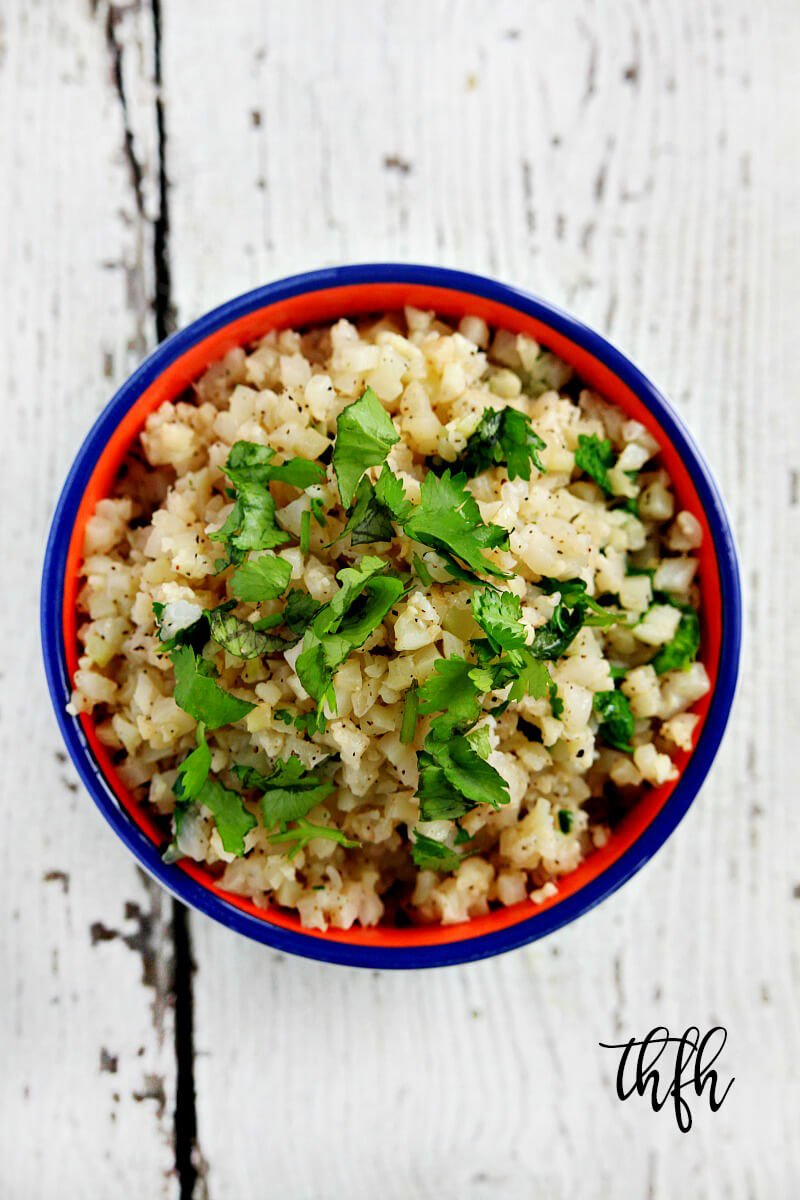 Vertical overhead shot of Lectin-Free Vegan Cilantro and Lime Cauliflower rice in a blue rimmed bowl on a white wooden surface