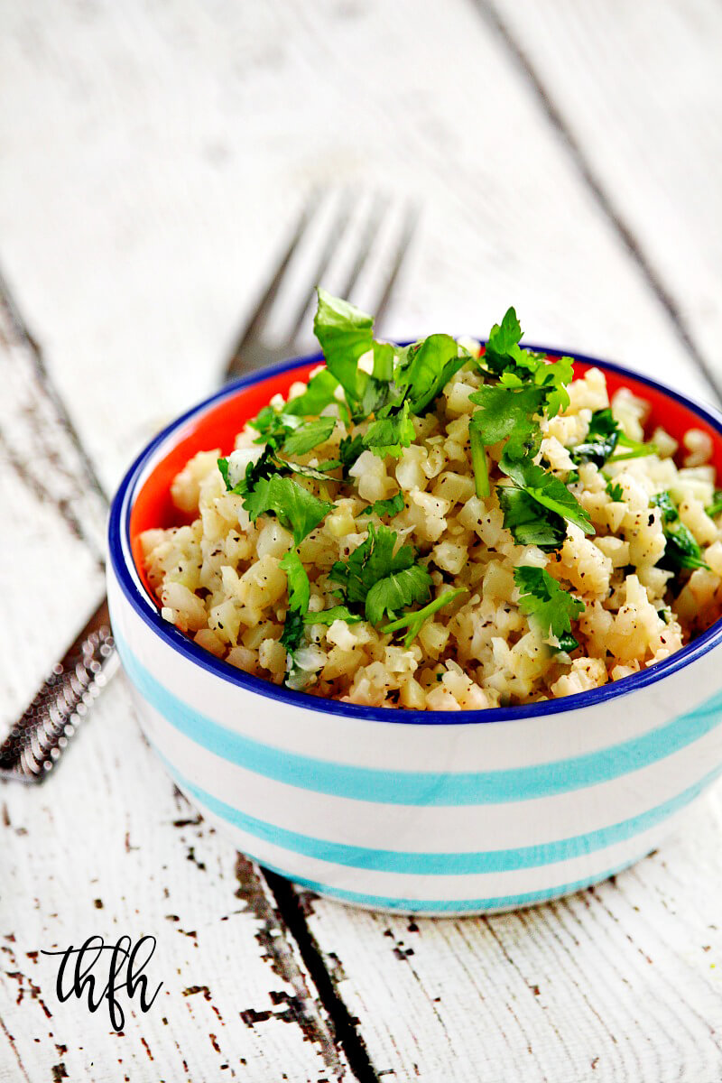 Vertical view of Lectin-Free Vegan Cilantro and Lime Cauliflower Rice in a blue and white striped bowl on a white wooden surface