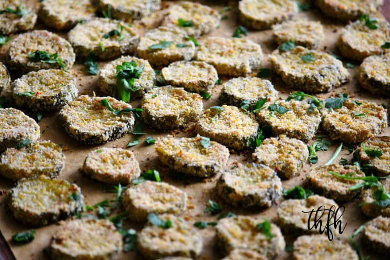 "Horizontal image of a baking pan full of Gluten-Free Vegan Oven-Baked ""Fried"" Pickles spread out evenly on top of parchment paper"