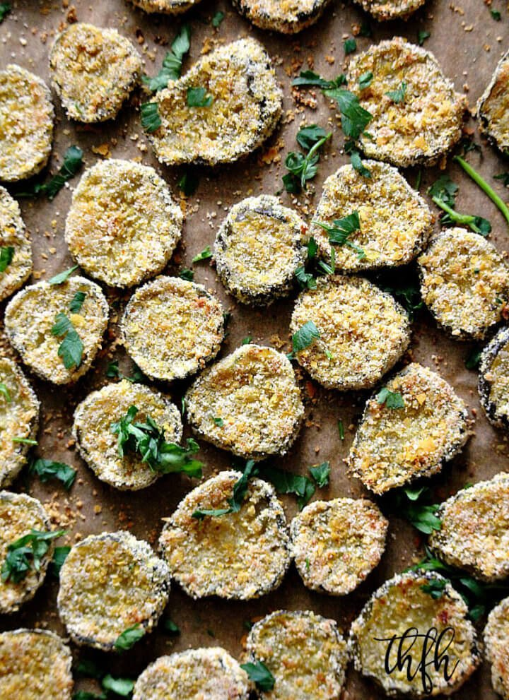 "Vertical image of a baking sheet full of Gluten-Free Vegan Oven-Baked ""Fried"" Pickles on top of parchment paper"