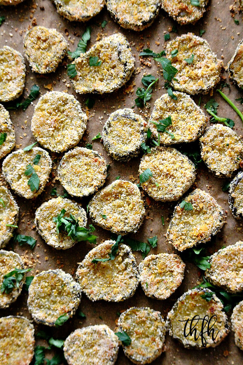 "Vertical image of a baking sheet full of The BEST Gluten-Free Vegan Oven-Baked ""Fried"" Pickles spread out evenly on top of parchment paper"