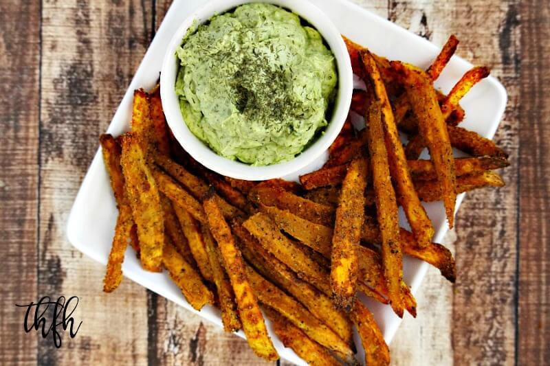 A white plate filled with Lectin-Free Vegan Spicy Turmeric Oven-Baked Sweet Potato Fries paired with a bowl of avocado dip on a weathered wooden background