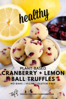 Gluten-Free Vegan Healthy No-Bake Cranberry Lemon Balls in a cream colored bowl surrounded by lemons and cranberries