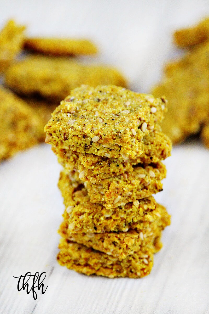 A stack of Gluten-Free Vegan Turmeric and Black Peppercorn Sesame Seed Crackers on a white wooden surface