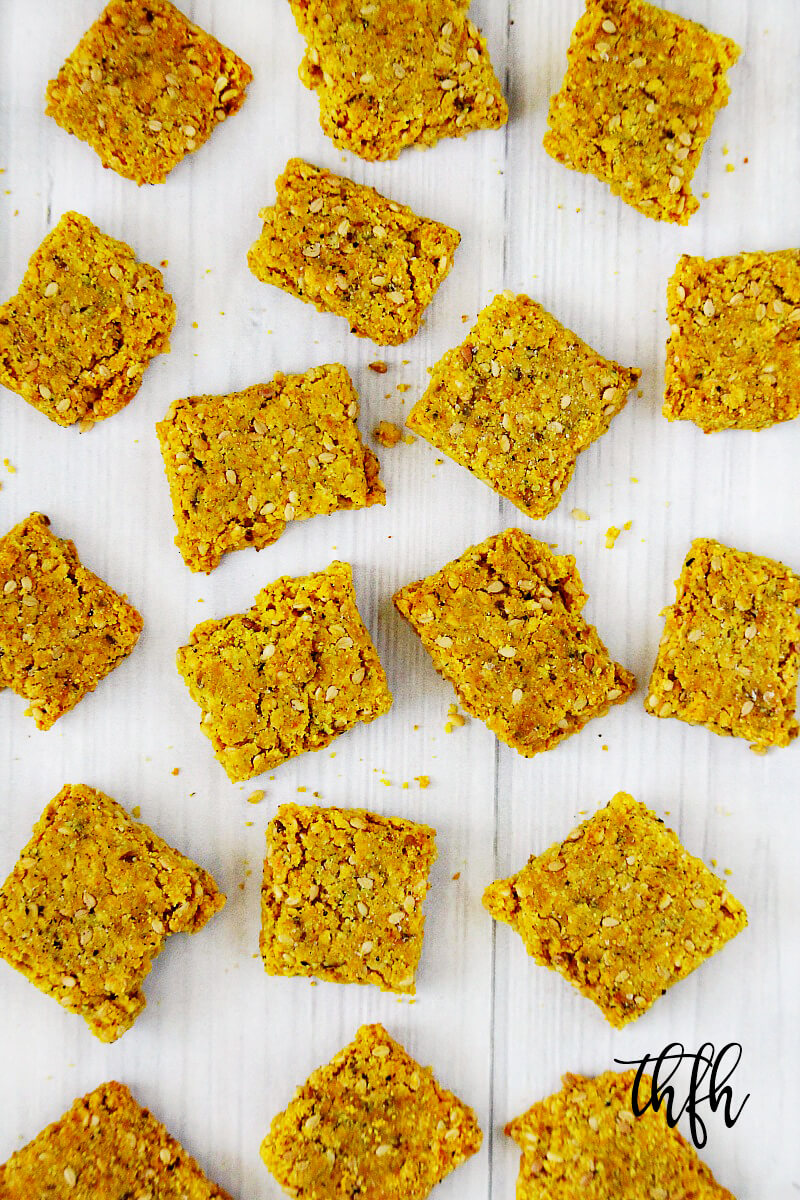 Overhead vertical view of Gluten-Free Vegan Turmeric and Black Peppercorn Sesame Seed Crackers on a white wooden surface