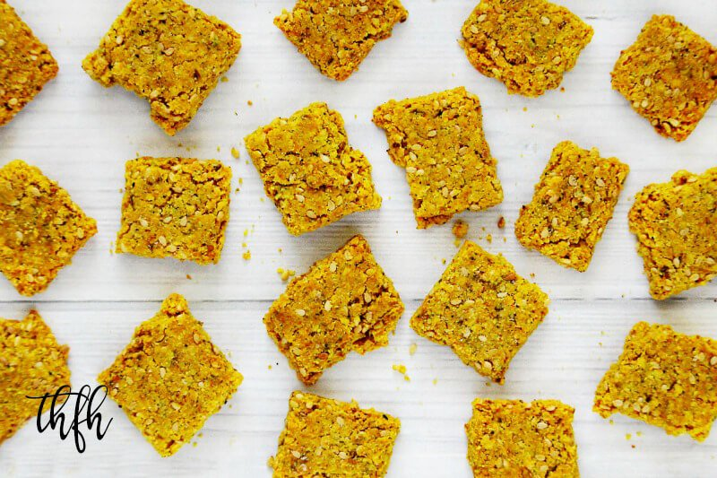 Overhead horizontal view of Gluten-Free Vegan Turmeric and Black Peppercorn Sesame Seed Crackers on a white wooden surface