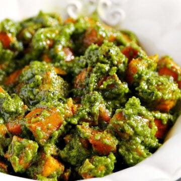 Vertical view of Lectin-Free and Gluten-Free Vegan Cilantro Pesto Sweet Potato Salad in a white bowl on a wooden surface