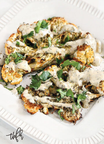 "Vertical view of Gluten-Free Vegan Roasted Cauliflower ""Steaks"" with Lemon Dill Tahini Sauce on a white plate on a white marble surface"