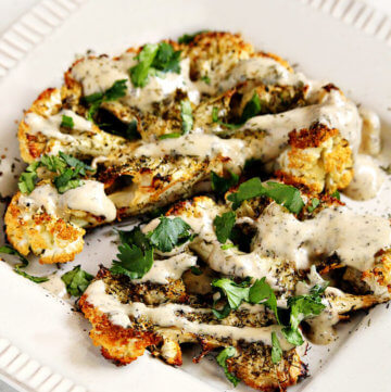 "Gluten-Free Vegan Roasted Cauliflower ""Steaks"" with Lemon Dill Tahini Dressing recipe...super easy to make and they're vegan, gluten-free, dairy-free, lectin-free, keto-friendly, paleo-friendly | thehealthyfamilyandhome.com #vegan #veganrecipes #glutenfree #paleo #lectinfree #lectinfreevegan #cleaneating #plantbased #healthy #healthyrecipes #healthyfood #cauliflower #dinner #recipe #dairyfree #nutfree #roastedcauliflower #cauliflowersteaks #medicalmedium"