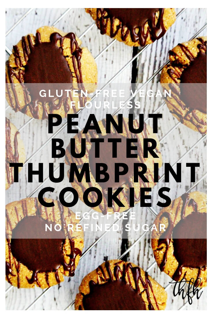 Overhead shot of Gluten-Free Vegan Flourless Chocolate Peanut Butter Thumbprint Cookies on a wire cookie rack on top of a white wooden surface