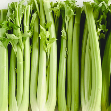 Vertical image of organic raw celery on a white marble surface