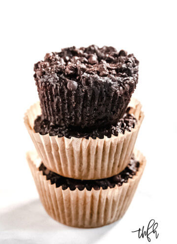 Vertical image of a stack of 3 Gluten-Free Vegan Flourless Chocolate Zucchini Muffins in paper muffin cups on a white background