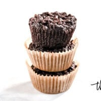 Horizontal view of a stack of 3 Gluten-Free Vegan Flourless Chocolate Zucchini Muffins in paper muffin cups on a white background