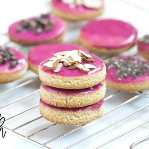 Horizontal view of a stack of 3 Gluten-Free Vegan Flourless Iced Cut-Out Cookies on wire cookie tray on a white surface