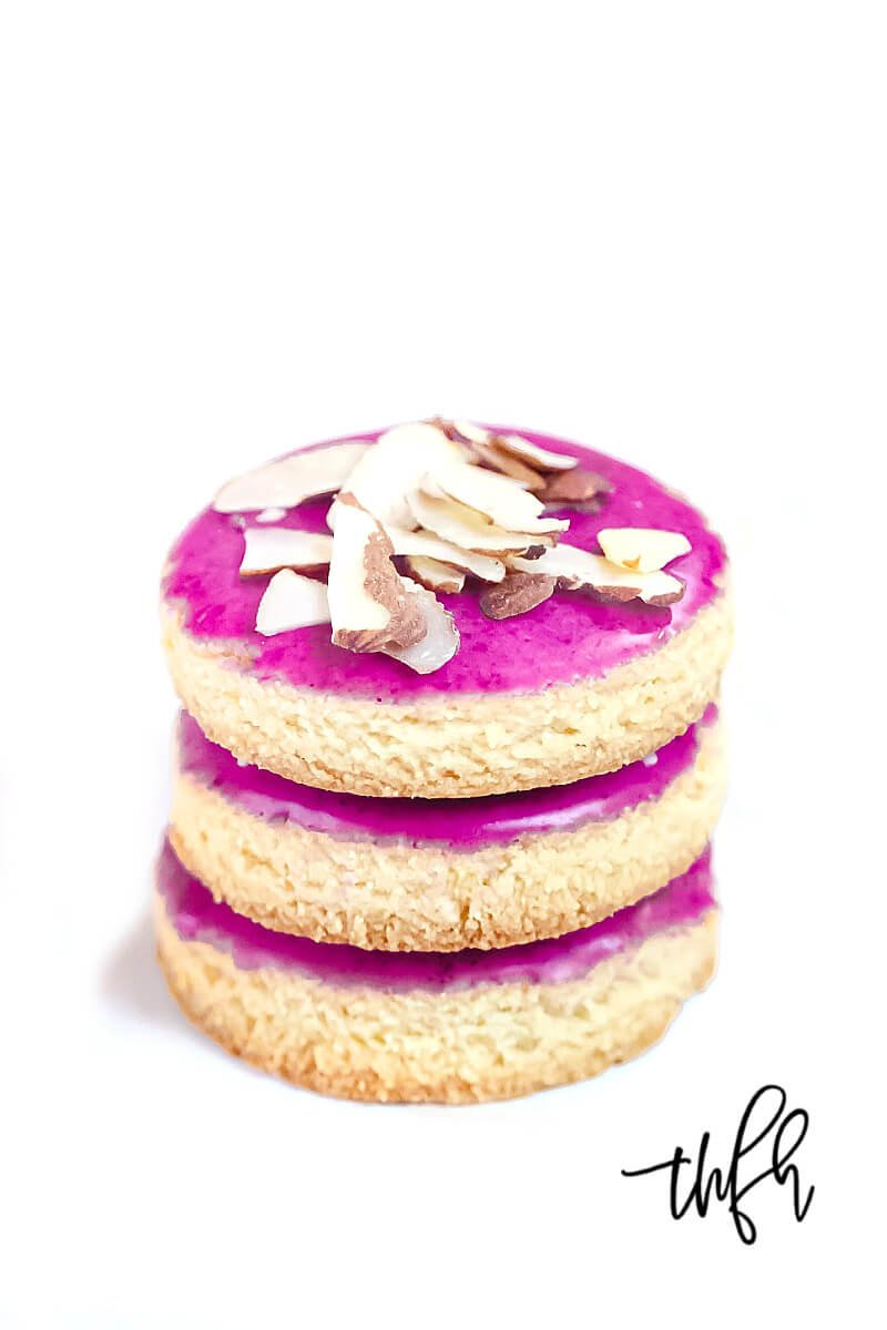 Vertical view of a stack of three Gluten-Free Vegan Flourless Iced Sugar Cut-Out Cookies on a wire cookie rack on a white surface