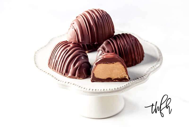4 Gluten-Free Vegan Healthy Reese's Peanut Butter Eggs on a small white pedestal on a white background