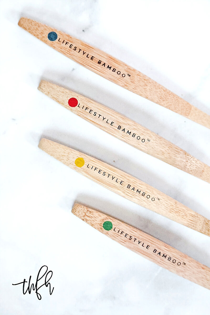 Four LIFESTYLE BAMBOO Eco-Friendly Bamboo Toothbrush handles with the brand logo on a white marble surface