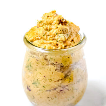 Vertical view of Gluten-Free Vegan Sweet Potato and Cilantro Dip in a glass jar on a white surface