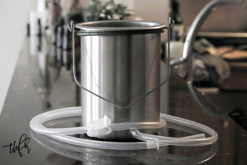 Horizontal view of a stainless steel coffee enema bucket with tubing