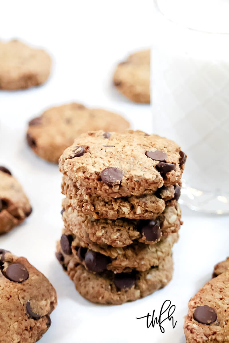 A stack of The BEST Gluten-Free Vegan Chocolate Chip Oatmeal Cookies in front of a glass of milk with cookies in the background