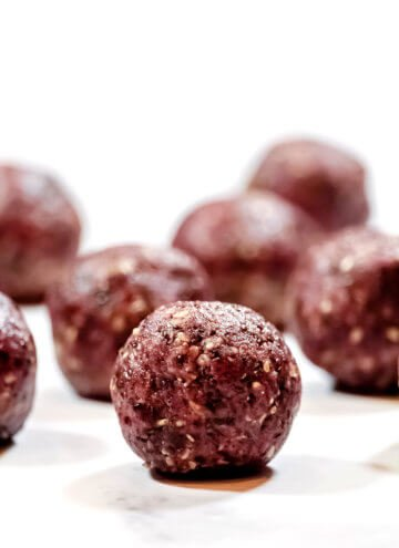 Vertical view of Gluten-Free Vegan Healthy No-Bake Triple Seed Energy Balls on a white surface
