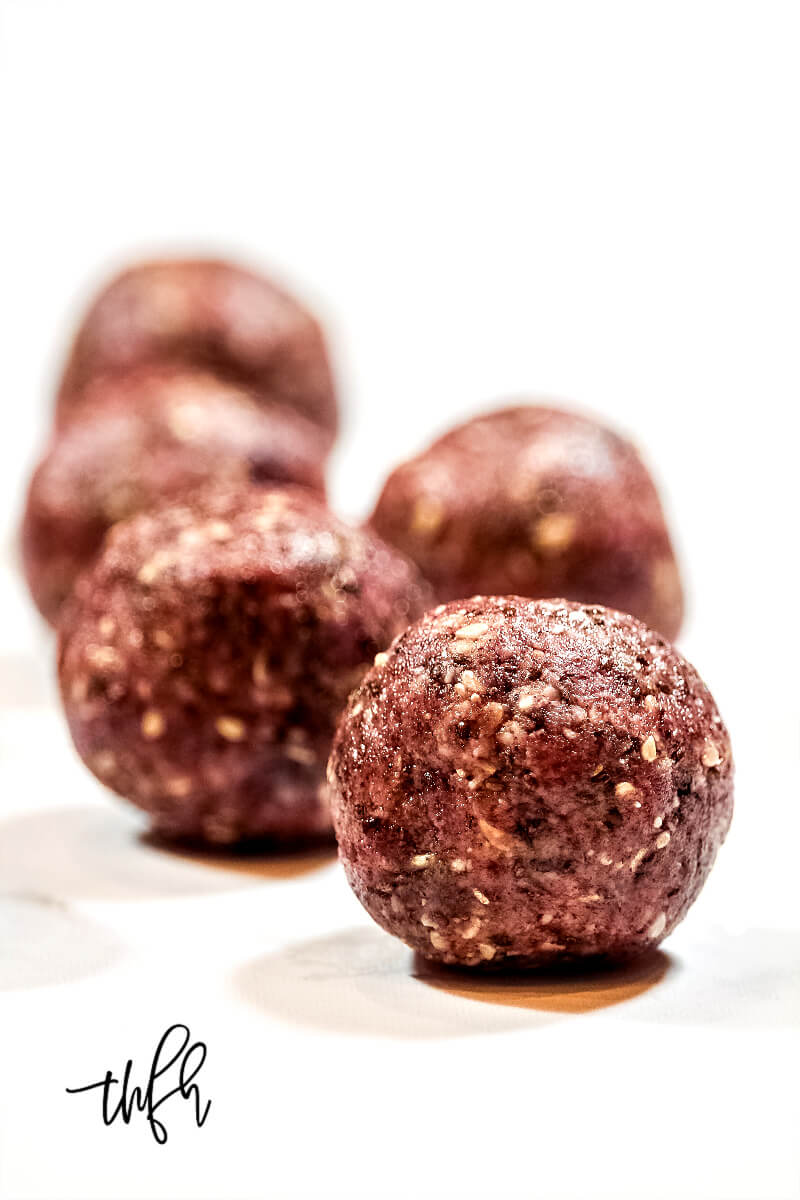 Vertical View of five Gluten-Free Vegan Healthy Triple Seed Energy Balls on a white surface