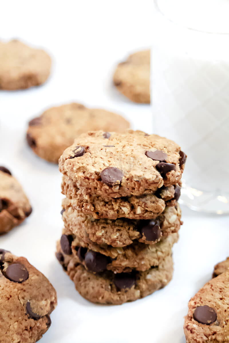 Vertical image of a stack of The BEST Gluten-Free Vegan Chocolate Chip Oatmeal Cookies on a white surface