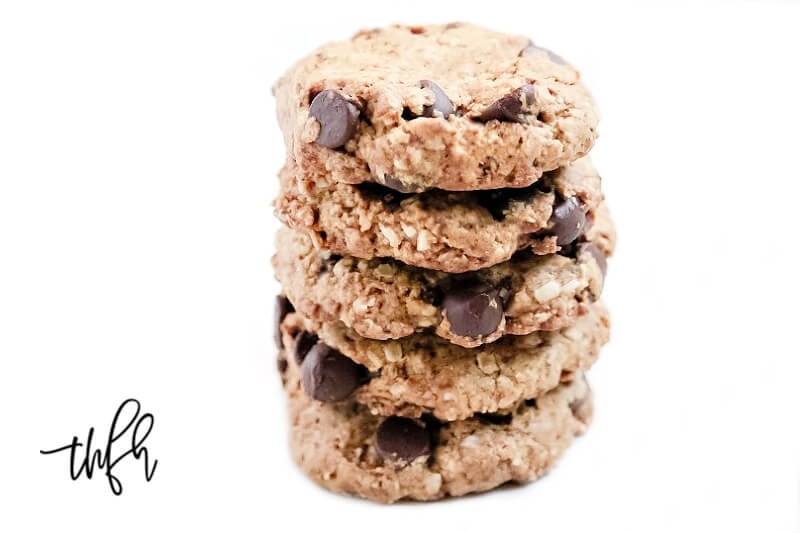 Four of The BEST Gluten-Free Vegan Chocolate Chip Oatmeal Cookies stacked on top of each other on a solid white background