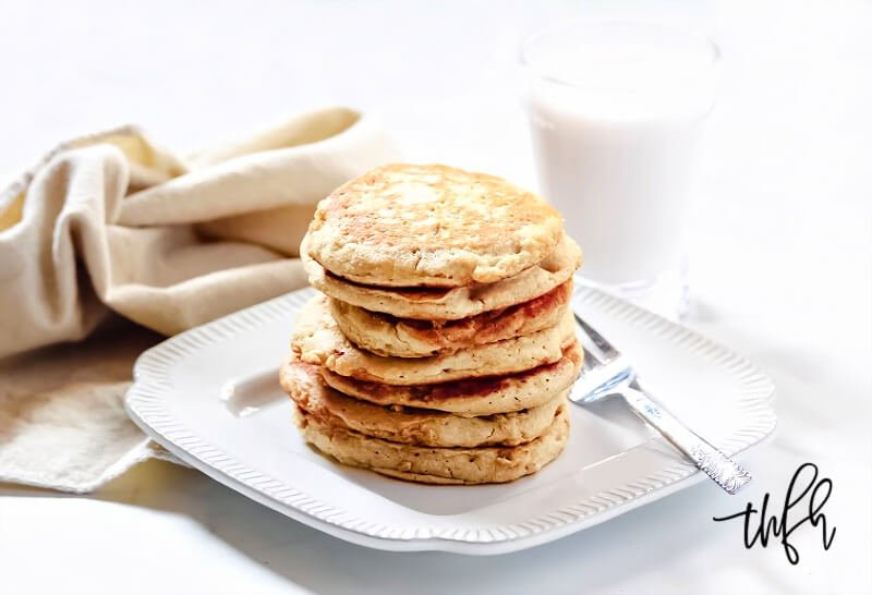 Horizontal image of a large stack of Gluten-Free Vegan Pumpkin Spice Blender Pancakes on a decorative white plate with a glass of milk and cream cloth napkin in the background