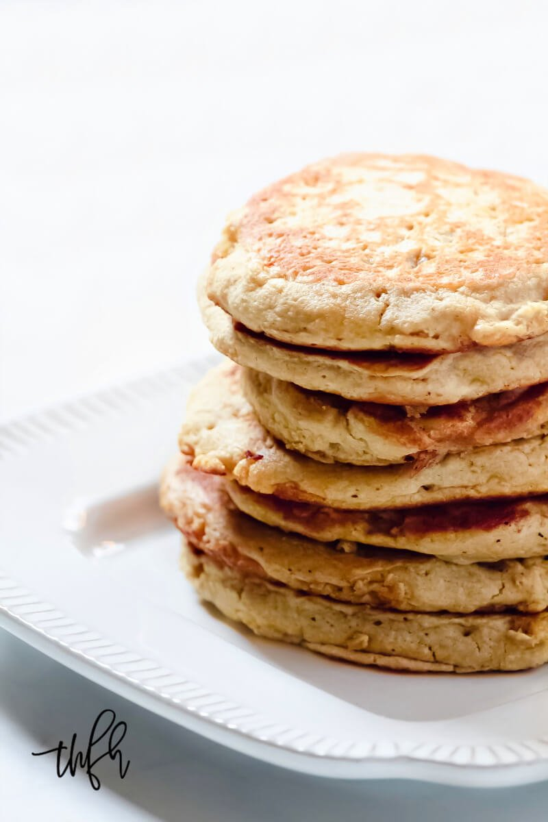 A close-up of a large stack of Gluten-Free Vegan Pumpkin Spice Blender Pancakes on a grey decorative plate