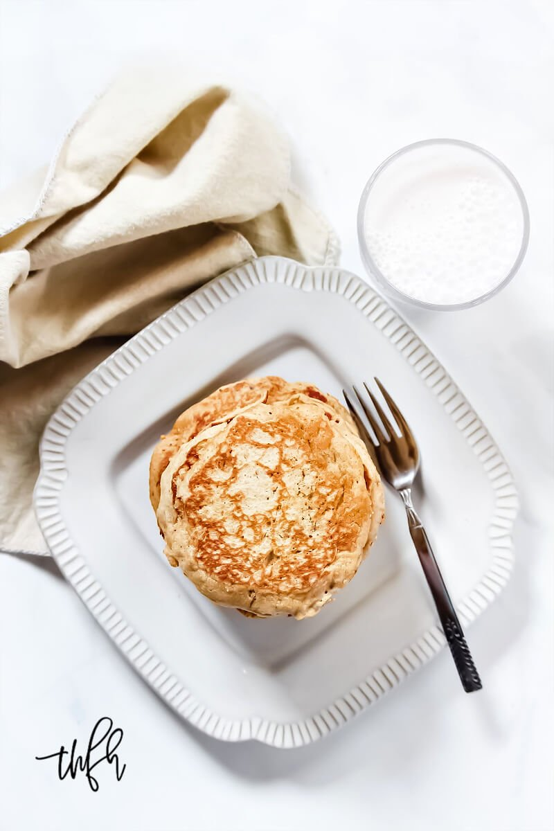 Overhead vertical image of a decorative grey plate with a stack of Gluten-Free Vegan Pumpkin Spice Pancakes on it and a glass of milk and cream cloth napkin to the side of it
