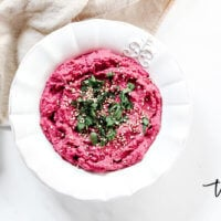Overhead view of a white bowl of The BEST Gluten-Free Vegan Spicy Jalapeno Beet Hummus with a tan napkin in the background on a solid white surface