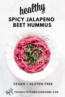 A decorative white bowl filled with The BEST Gluten-Free Vegan Spicy Jalapeno Beet Hummus on a solid white background with text overlay