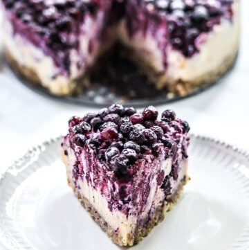 A single slice of Gluten-Free Vegan No-Bake Wild Blueberry Cheesecake on a small grey plate with the entire cheesecake in the background