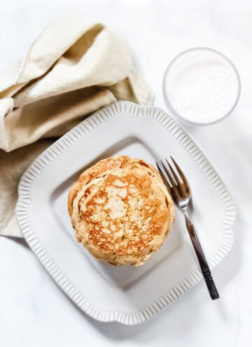 Overhead image of a decorative grey plate with a stack of Gluten-Free Vegan Pumpkin Spice Blender Pancakes on it with a glass of milk and cream cloth napkin to the side of the plate